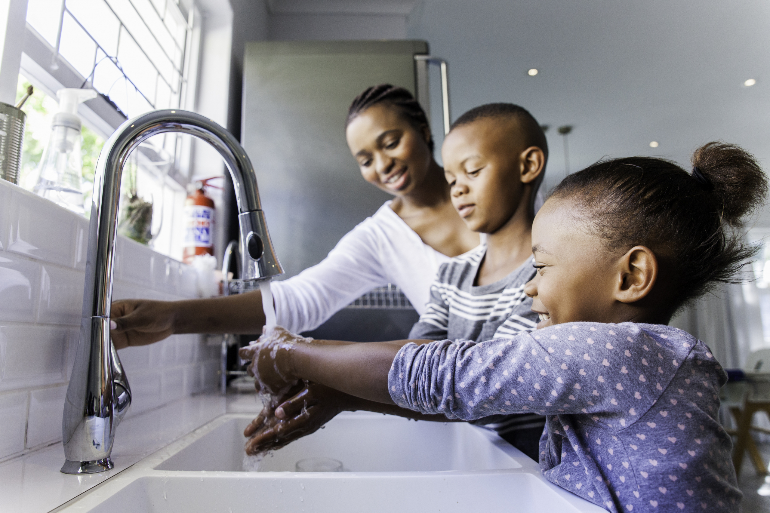 Mother and children washing hands